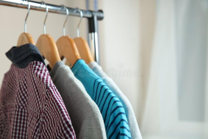 Vêtements du ` s d'enfants sur un cintre images stock