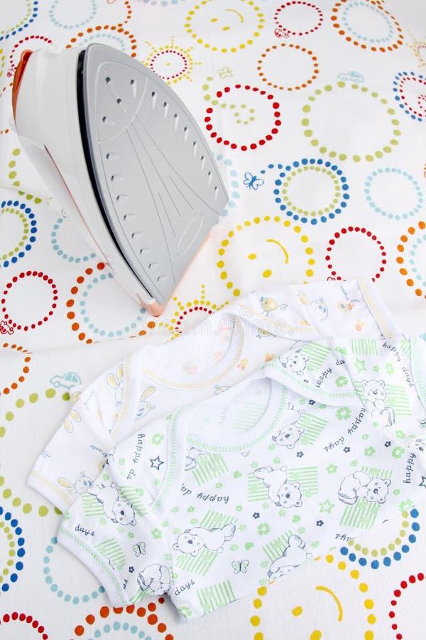 Vêtements et fer de bébé sur la planche à repasser sur le fond coloré avec l'espace de copie images stock