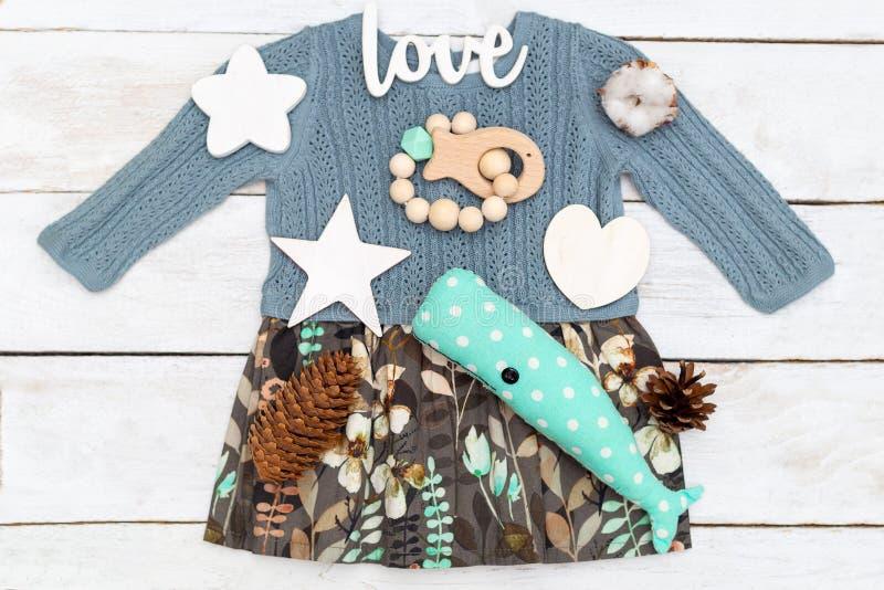 Vêtements et jouets de bébé sur un fond en bois Configuration plate image stock
