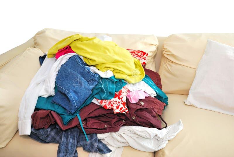 Vêtements malpropres sur le sofa images stock