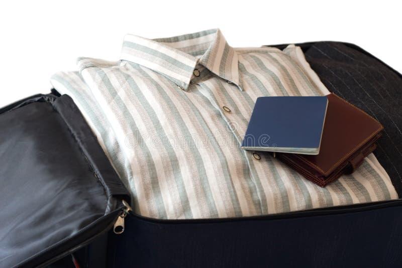 Vêtements, pochette et passeport d'isolement images stock