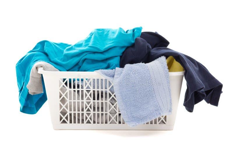 Vêtements sales dans un panier de blanchisserie d'isolement sur le blanc photos stock