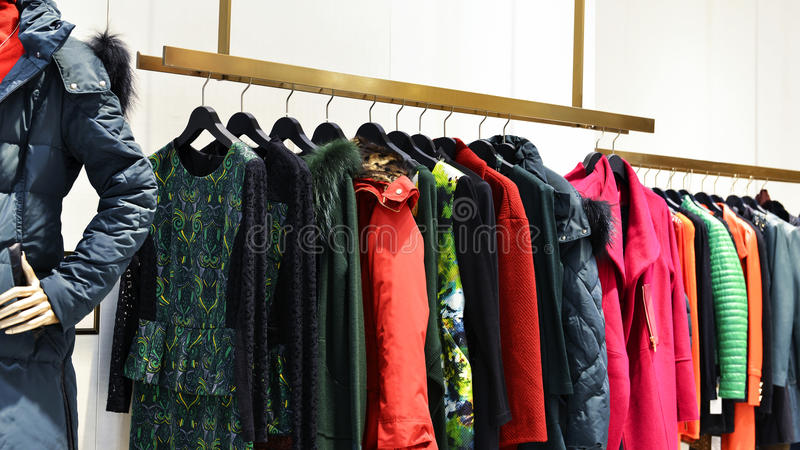 Vêtements sur des supports dans la boutique de mode photographie stock