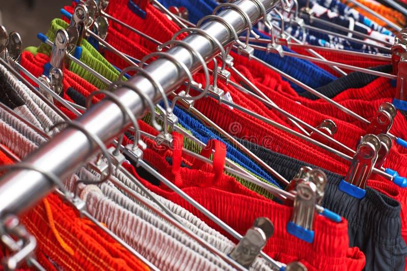 Vêtements vifs accrochant sur des cintres dans la boutique photographie stock