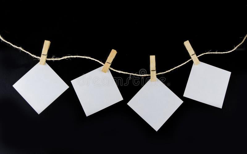 Vêtez la goupille sur la corde avec la note de papier sur le fond noir image libre de droits