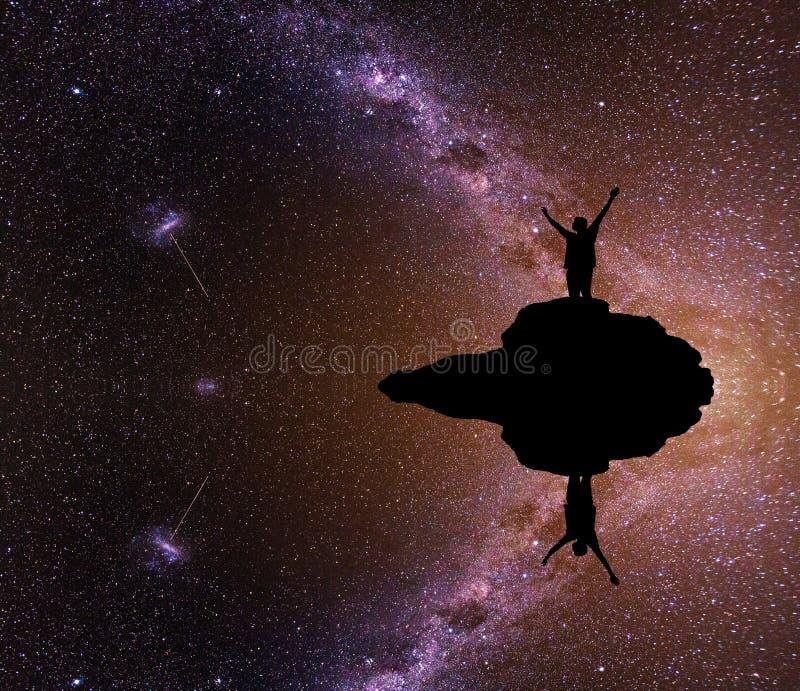 Vía láctea Cielo nocturno hermoso con las estrellas y la silueta de un hombre solo de la situación en la montaña imagen de archivo libre de regalías