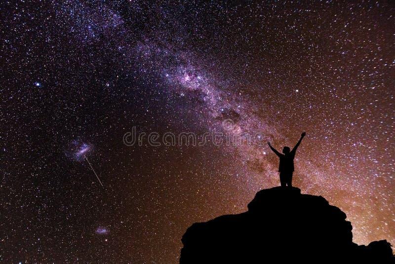Vía láctea Cielo nocturno hermoso con las estrellas y la silueta de un hombre solo de la situación en la montaña imagen de archivo