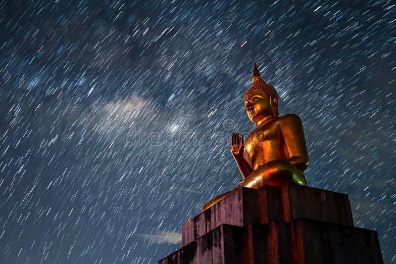 Vía láctea grande de la noche de la estrella de la estatua de Buda imagenes de archivo