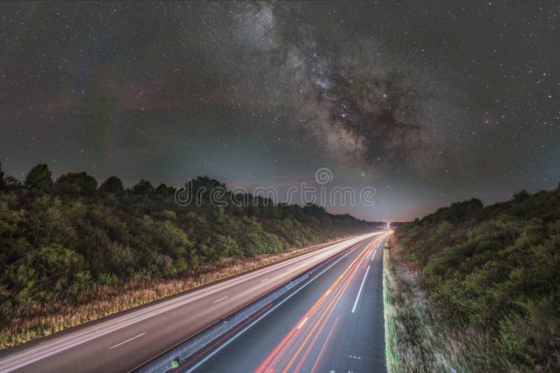 Vía láctea sobre la carretera fotografía de archivo