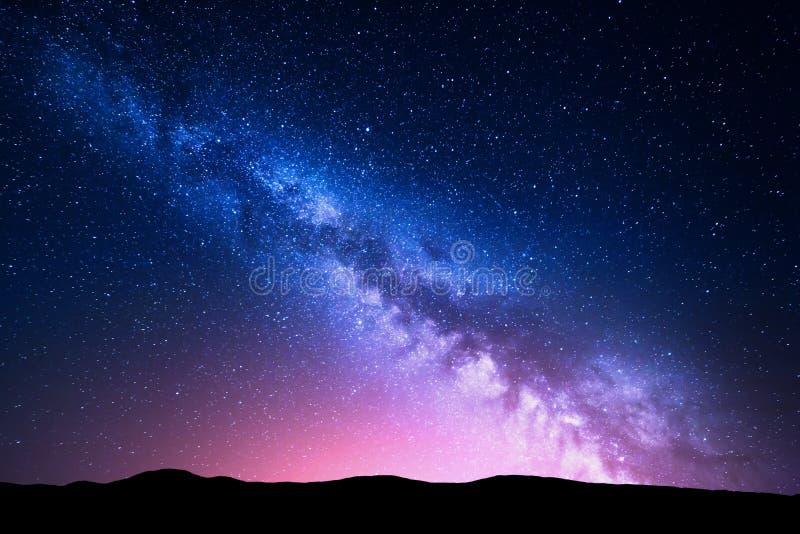 Vía láctea y luz rosada en las montañas Paisaje colorido de la noche imagen de archivo libre de regalías