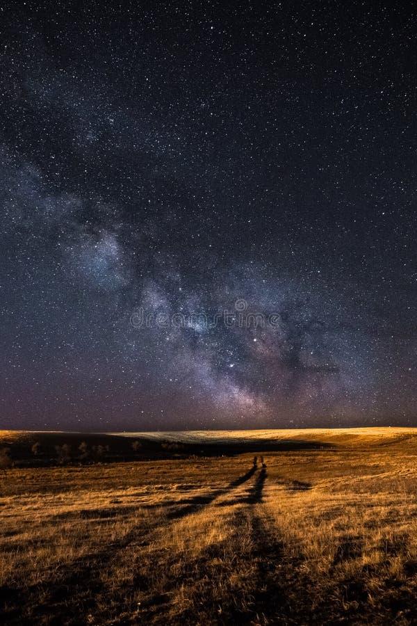 Vía láctea y una trayectoria en el campo fotografía de archivo