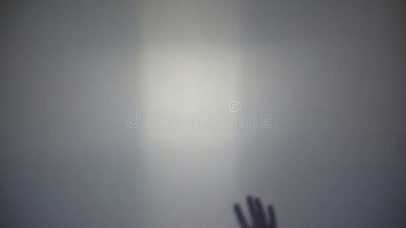 Víctima del asesino que pide la ayuda, mano en la pared transparente, crimen de la persona fotografía de archivo