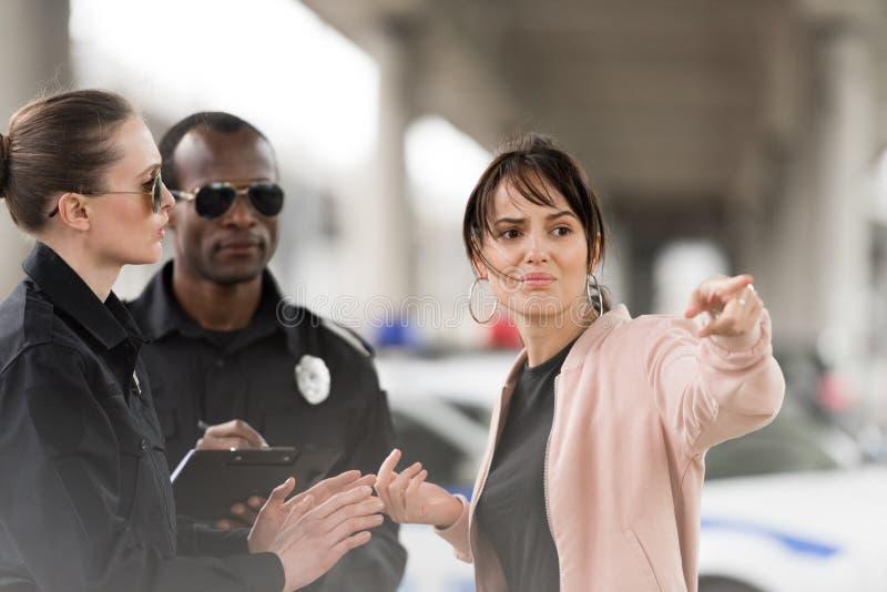 víctima femenina joven asustada que señala por el finger a la mujer policía imagen de archivo