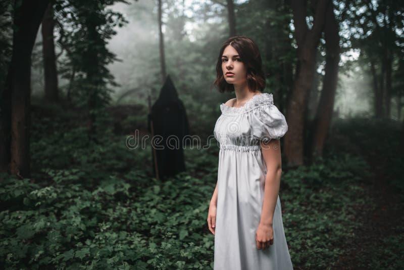 Víctima femenina y muerte en sudadera con capucha negra en bosque fotografía de archivo