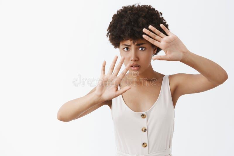 Víctima que se convierte de la violencia familiar, siendo asustado del sacador, cara de la cubierta, protegiendo ella misma de la fotografía de archivo libre de regalías