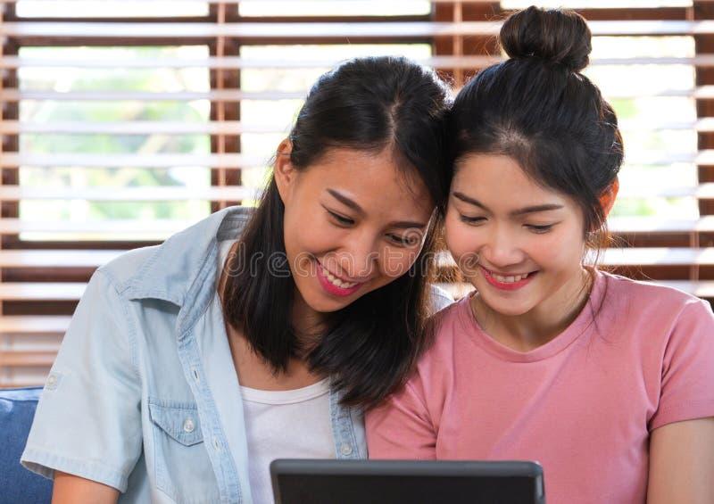 Vídeo de observação da lésbica asiática feliz na tabuleta no sofá na casa Conceito do estilo de vida de LGBTQ fotos de stock royalty free