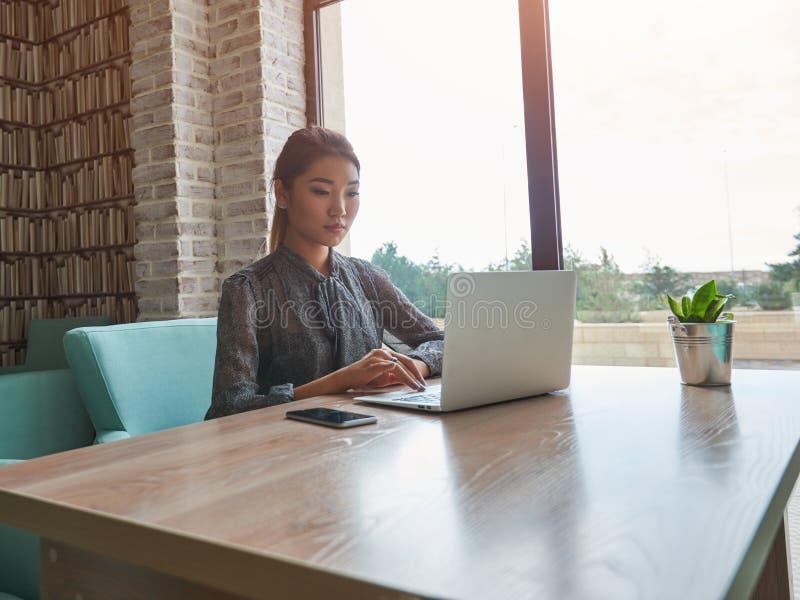 Vídeo de observação da mulher alegre no laptop ao esperar sua ordem no café acolhedor do passeio fotos de stock