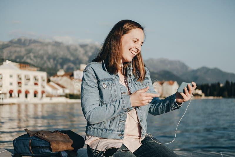 Vídeo de observação da mulher feliz no telefone no cais perto do mar foto de stock royalty free