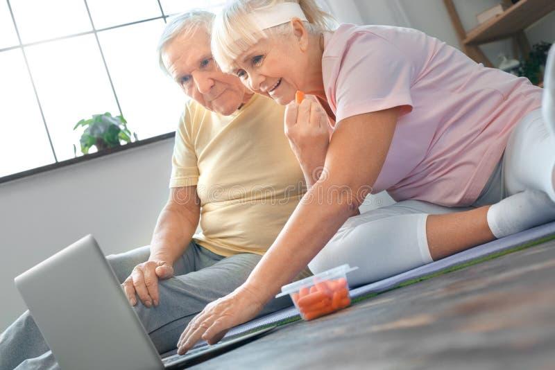 Vídeo de observação dos pares do exercício dos cuidados médicos superiores junto em casa concentrado fotografia de stock