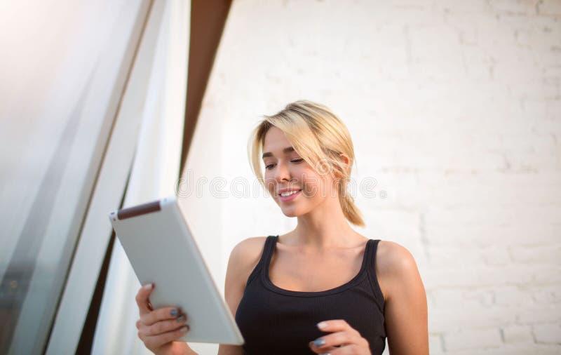 Vídeo de observação de sorriso bonito novo da mulher no Internet através da tabuleta digital, estando no interior moderno fotografia de stock royalty free