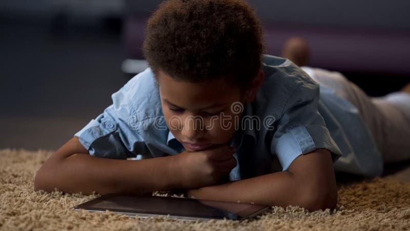 Vídeo de observación del niño en la tableta, agujereada en casa, ocio mal organizado para el niño imagen de archivo libre de regalías