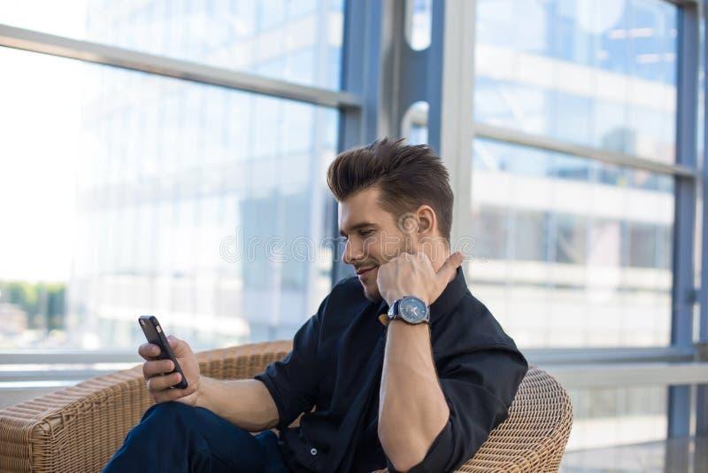 Vídeo de observación de la dirección masculina alegre en smartphone durante rotura de trabajo imagen de archivo libre de regalías