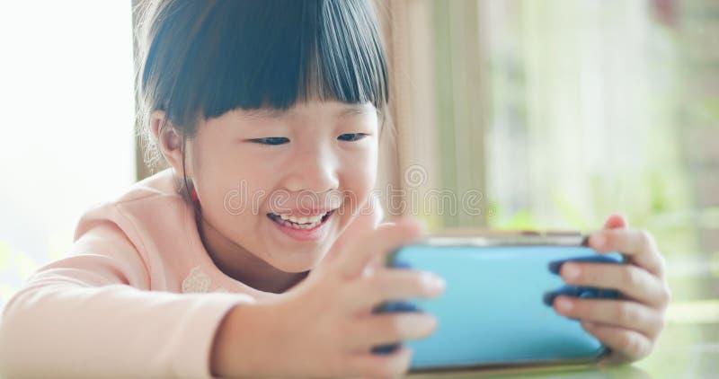 Vídeo do relógio da menina pelo telefone imagem de stock royalty free