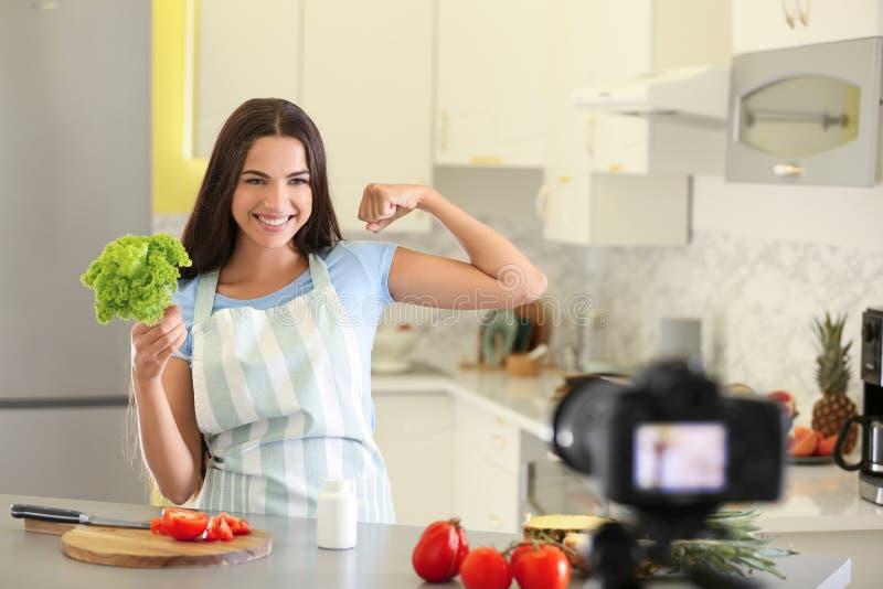 Vídeo fêmea novo da gravação do blogger do alimento na cozinha imagem de stock royalty free