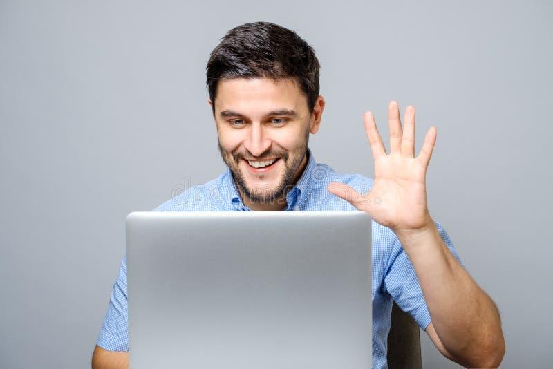 Vídeo feliz del hombre joven que charla en el ordenador portátil foto de archivo