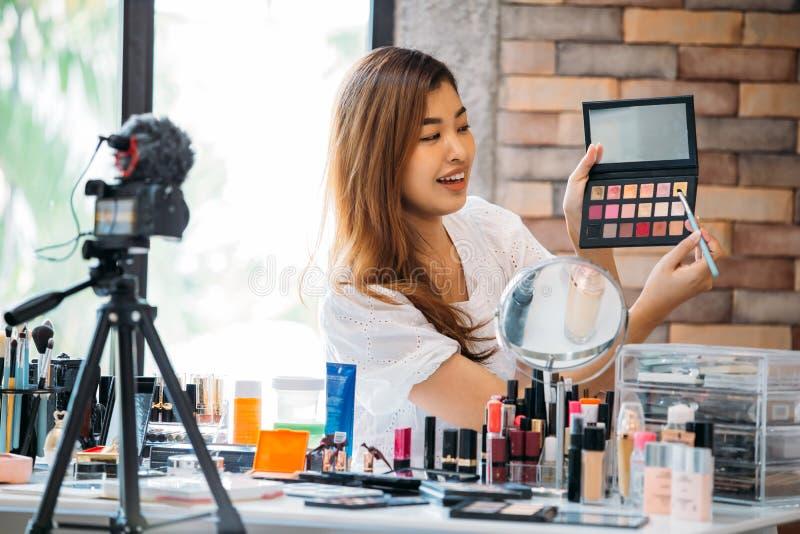 Vídeo preceptoral de registración del maquillaje de la mujer asiática bonita sobre los cosméticos con el teléfono móvil en el trí fotografía de archivo