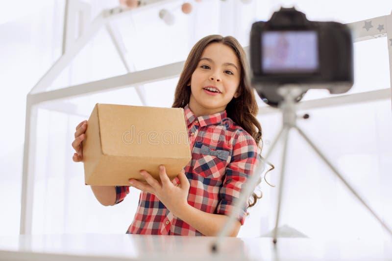 Vídeo unboxing da gravação alegre da menina na câmera fotos de stock royalty free