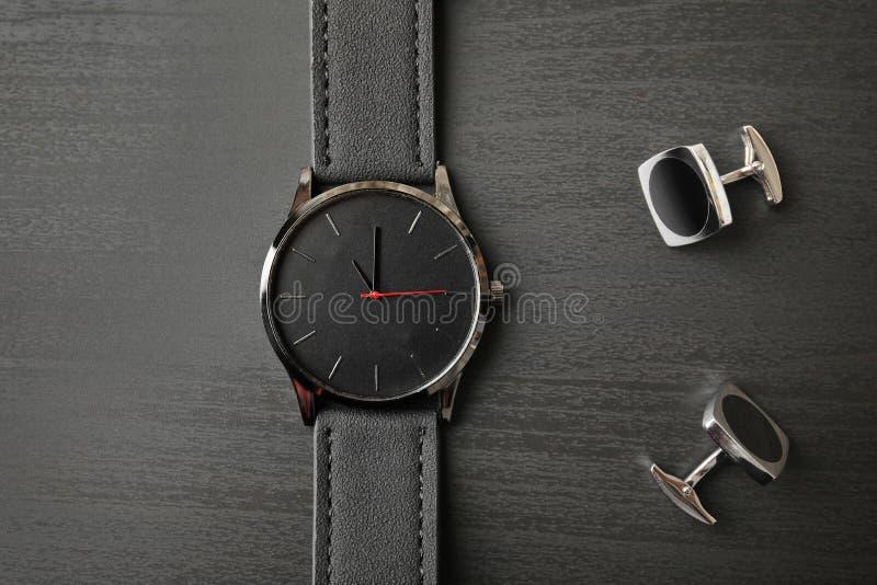 Vínculos elegantes del reloj y de puño en el fondo de madera, visión superior foto de archivo