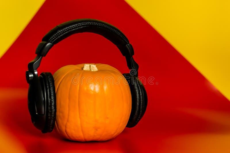 Víspera de Todos los Santos auriculares anaranjados del negro de la calabaza con un espacio vacío en rojo con un fondo amarillo imágenes de archivo libres de regalías