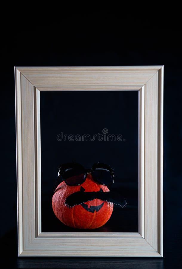 Víspera de Todos los Santos divertida Calabaza en lentes de sol negros y bigote en el fondo negro Muchacho del padre del hombre d fotos de archivo