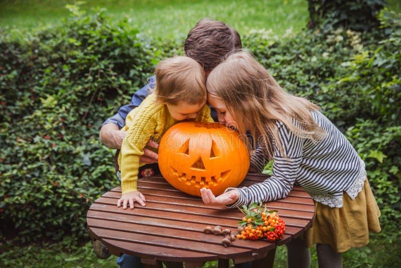 Víspera de Todos los Santos feliz El padre y dos hijas miran el interior la calabaza tallada para Halloween afuera fotos de archivo