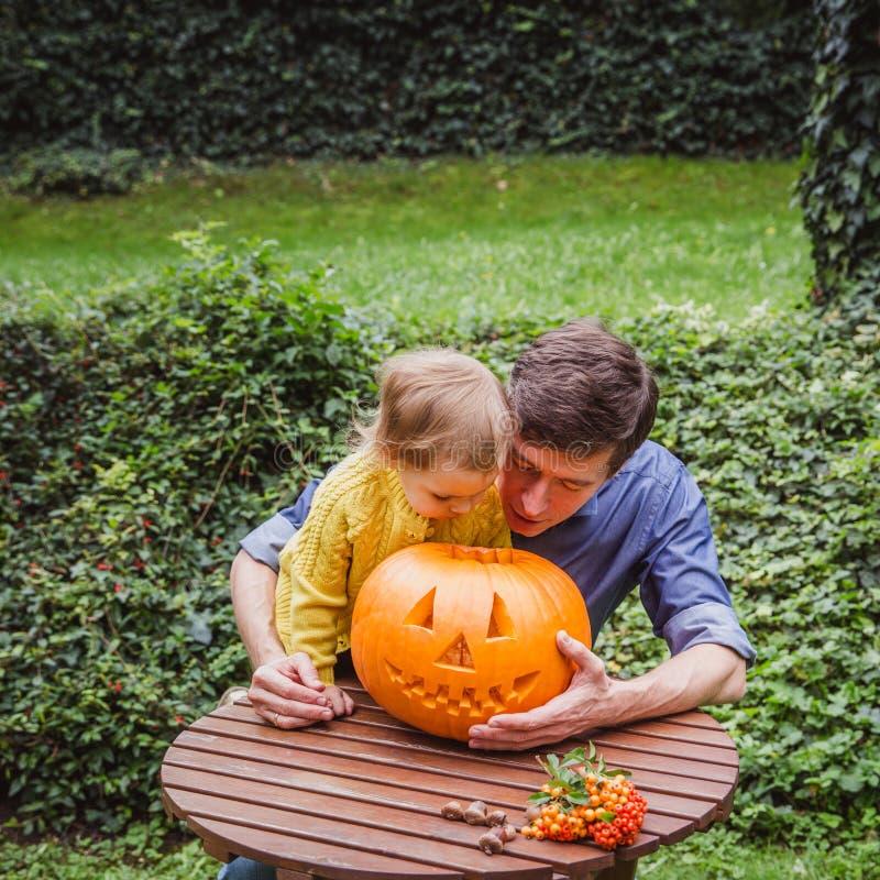 Víspera de Todos los Santos feliz El padre y la hija miran el interior la calabaza tallada para Halloween afuera imagenes de archivo