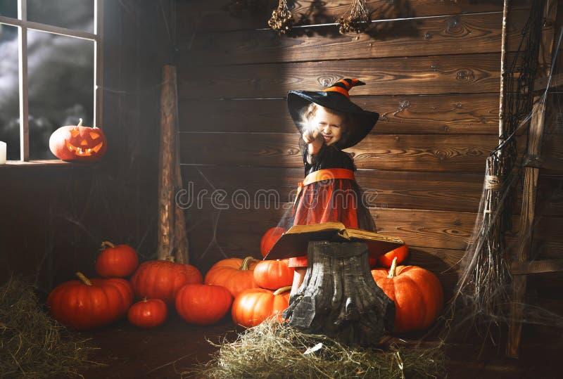 Víspera de Todos los Santos la pequeña bruja conjura con el libro de encantos, magia fotografía de archivo