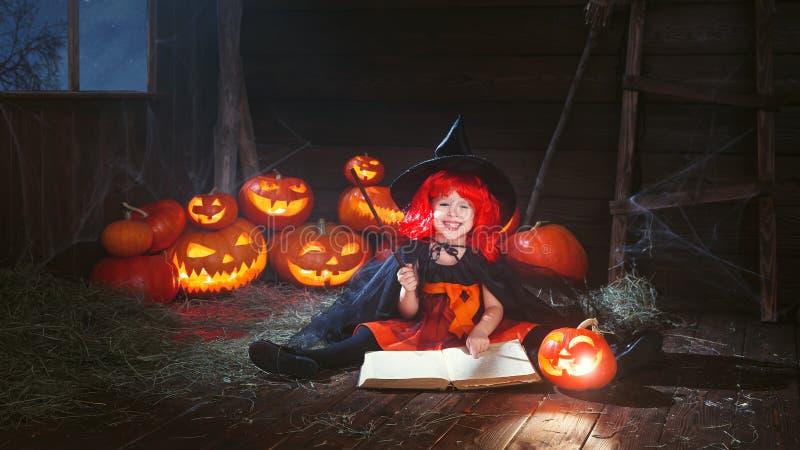 Víspera de Todos los Santos la pequeña bruja conjura con el libro de encantos, magia fotos de archivo