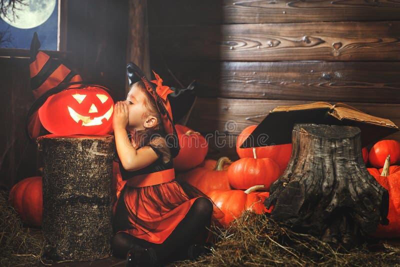 Víspera de Todos los Santos la pequeña bruja conjura con el libro de encantos, magia foto de archivo