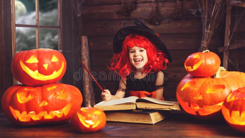 Víspera de Todos los Santos la pequeña bruja conjura con el libro de encantos, unos de los reyes magos foto de archivo libre de regalías