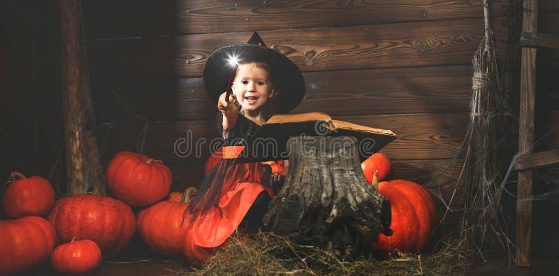 Víspera de Todos los Santos la pequeña bruja conjura con el libro de encantos, unos de los reyes magos imagen de archivo libre de regalías