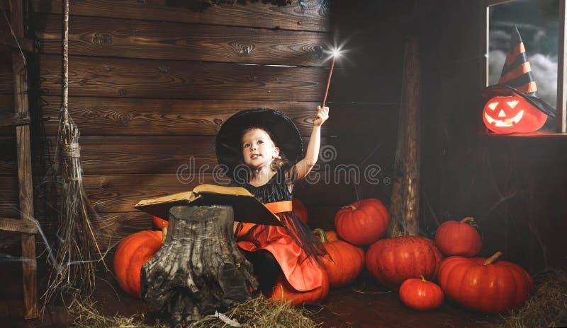 Víspera de Todos los Santos la pequeña bruja conjura con el libro de encantos, unos de los reyes magos fotografía de archivo libre de regalías