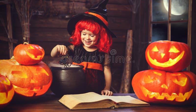 Víspera de Todos los Santos la pequeña bruja conjura con el libro de encantos, unos de los reyes magos fotos de archivo