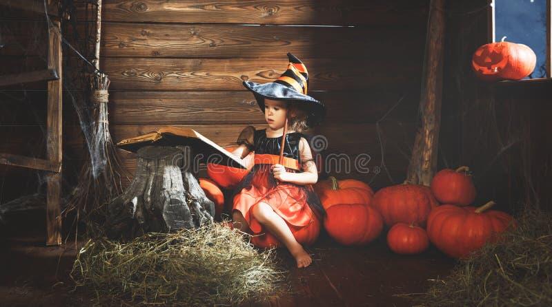 Víspera de Todos los Santos la pequeña bruja conjura con el libro de encantos, unos de los reyes magos imagenes de archivo