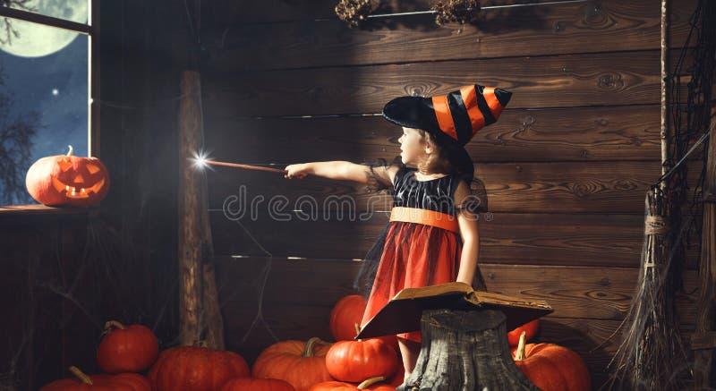 Víspera de Todos los Santos la pequeña bruja conjura con el libro de encantos, unos de los reyes magos fotografía de archivo