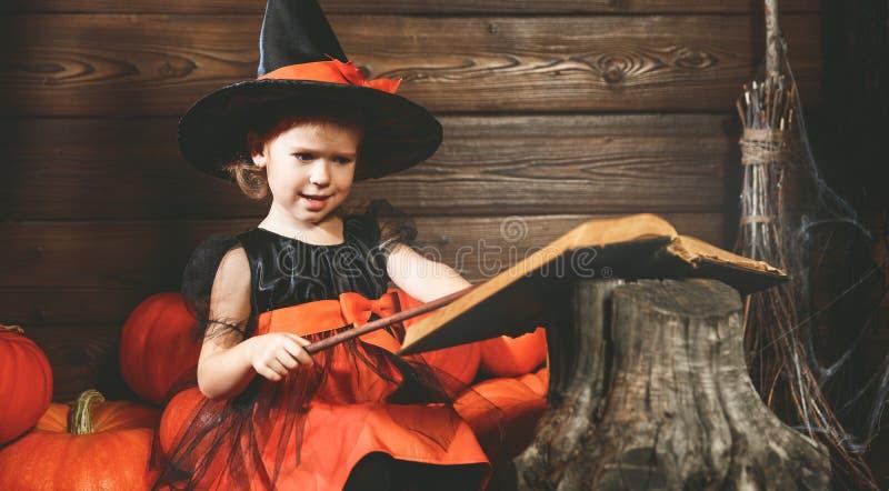Víspera de Todos los Santos la pequeña bruja conjura con el libro de encantos, unos de los reyes magos foto de archivo