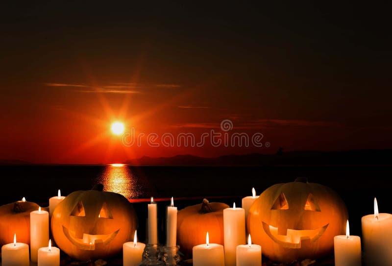 Víspera de Todos los Santos Levante la linterna, calabazas anaranjadas, velas, puesta del sol, sol, mar, foto de archivo libre de regalías