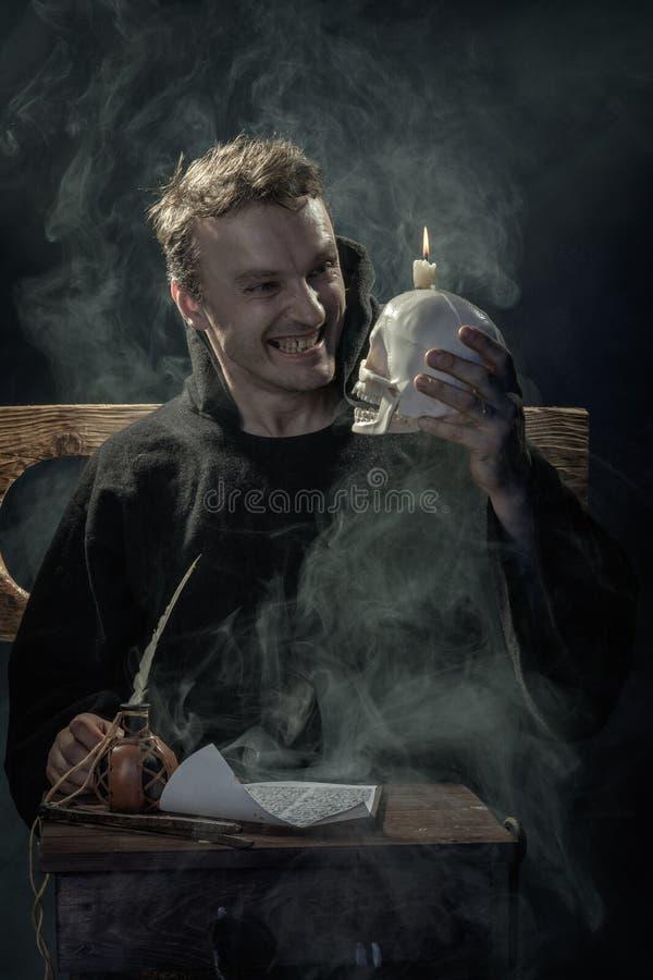 Víspera de Todos los Santos Monje de risa con un cráneo en su mano imagen de archivo