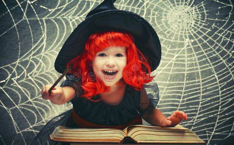 Víspera de Todos los Santos pequeña bruja alegre con el conjur mágico de la vara y del libro foto de archivo libre de regalías