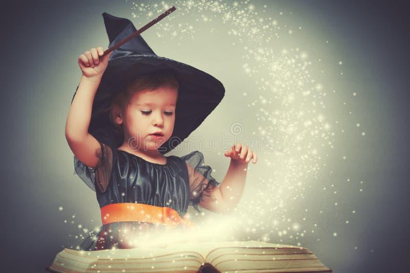 Víspera de Todos los Santos pequeña bruja alegre con una vara mágica y un b que brilla intensamente foto de archivo